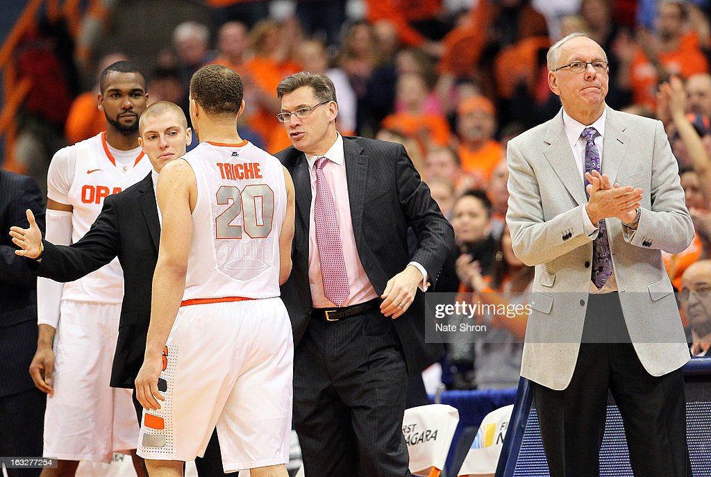 Head coach <a gi-track='captionPersonalityLinkClicked' href=/galleries/search?phrase=Jim+Boeheim&family=editorial&specificpeople=210990 ng-click='$event.stopPropagation()'>Jim Boeheim</a> (R) of the Syracuse Orange cheers as <a gi-track='captionPersonalityLinkClicked' href=/galleries/search?phrase=Brandon+Triche&family=editorial&specificpeople=6516120 ng-click='$event.stopPropagation()'>Brandon Triche</a> #20 exits the court, shaking hands with director of men's basketball operations Tim O'Toole (C), head manager Kevin Belbey (L) and James Southerland #43 on seniors night during the game against the DePaul Blue Demons during the game at the Carrier Dome on March 6, 2013 in Syracuse, New York.