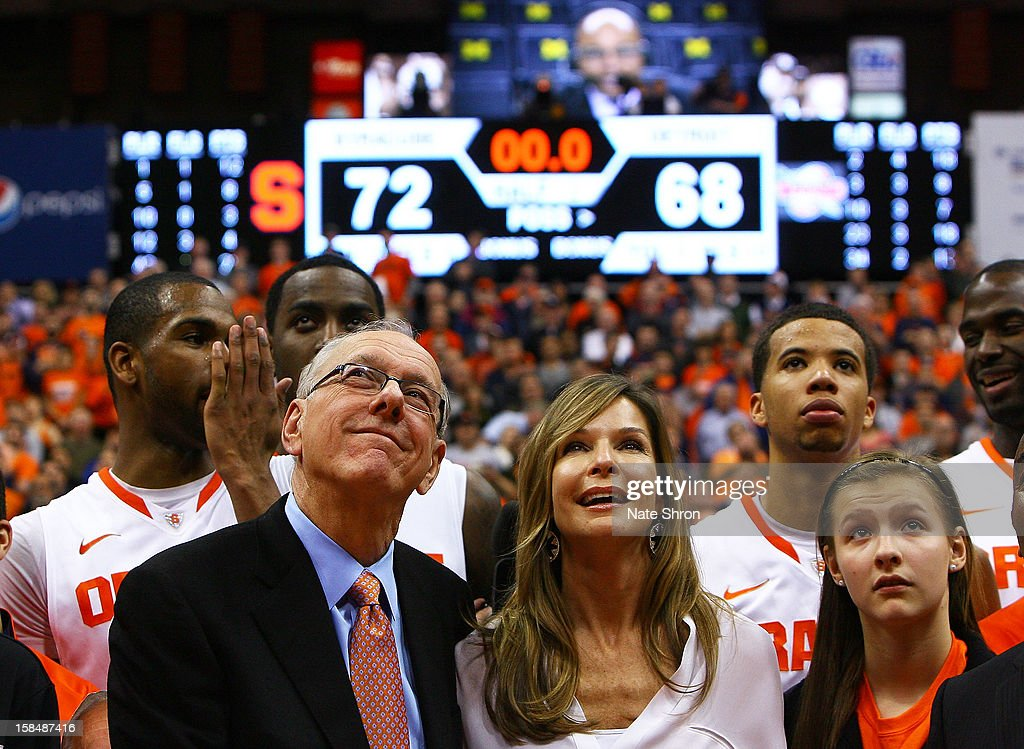 Head coach <a gi-track='captionPersonalityLinkClicked' href=/galleries/search?phrase=Jim+Boeheim&family=editorial&specificpeople=210990 ng-click='$event.stopPropagation()'>Jim Boeheim</a> of the Syracuse Orange looks on to the video screens as he stands next to wife, Juli Boeheim and daughter Jamie Boeheim to watch a presentation on the court after his 900th career win after the game against the Detroit Titans at the Carrier Dome on December 17, 2012 in Syracuse, New York.