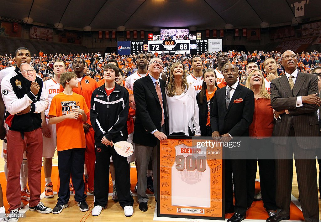 Head coach Jim Boeheim of the Syracuse Orange smiles as he stands next to wife Juli Boeheim, daughter Jamie Boeheim, director of athletics Daryl Gross and the mayor of Detroit Dave Bing as they look up to the video screens during a presentation on the court after his 900th career win after the game against the Detroit Titans during the game at the Carrier Dome on December 17, 2012 in Syracuse, New York.