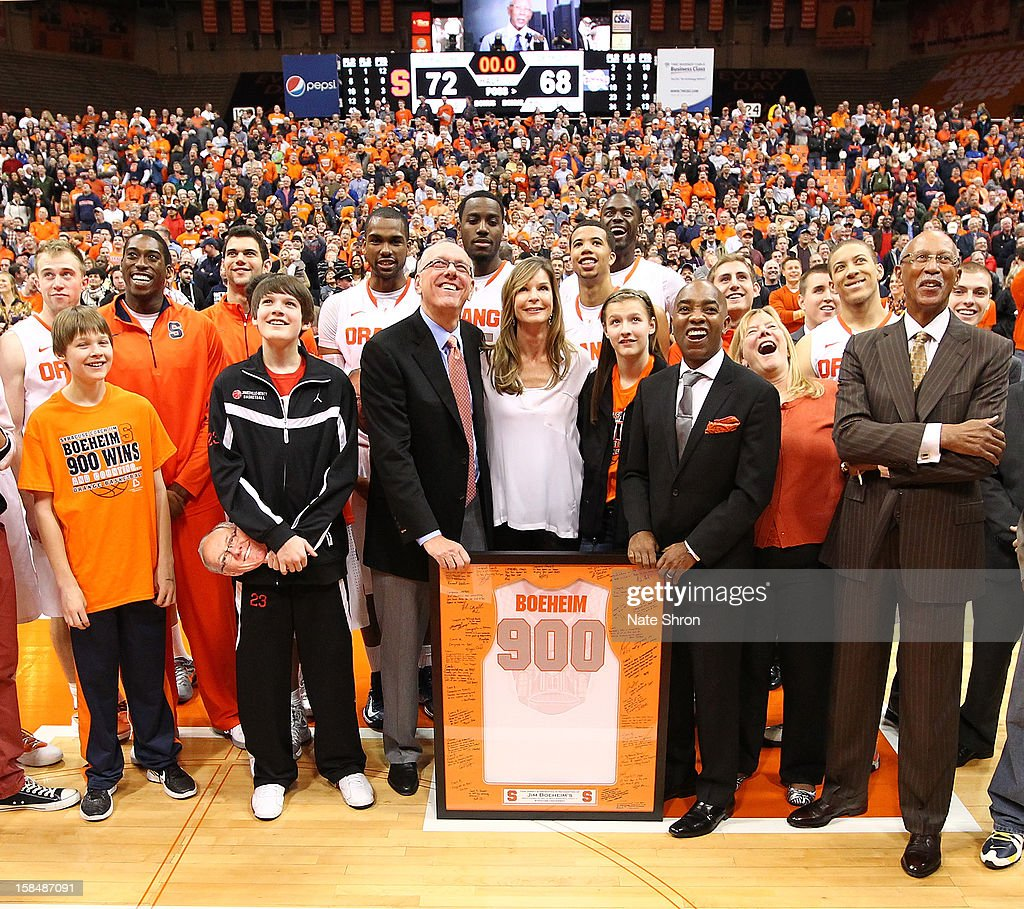 Head coach Jim Boeheim of the Syracuse Orange stands next to wife Juli Boeheim, daughter Jamie Boeheim, director of athletics Daryl Gross and Mayor of Detroit Dave Bing during a presentation on the court after his 900th career win after the game against the Detroit Titans during the game at the Carrier Dome on December 17, 2012 in Syracuse, New York.