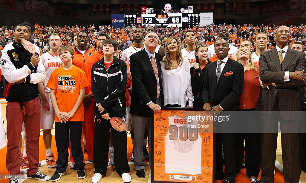 Head coach Jim Boeheim of the Syracuse Orange stands next to wife Juli Boeheim, daughter Jamie Boeheim, director of athletics Daryl Gross and the mayor of Detroit Dave Bing as they look up to the video screens during a presentation on the court after his 900th career win after the game against the Detroit Titans during the game at the Carrier Dome on December 17, 2012 in Syracuse, New York.