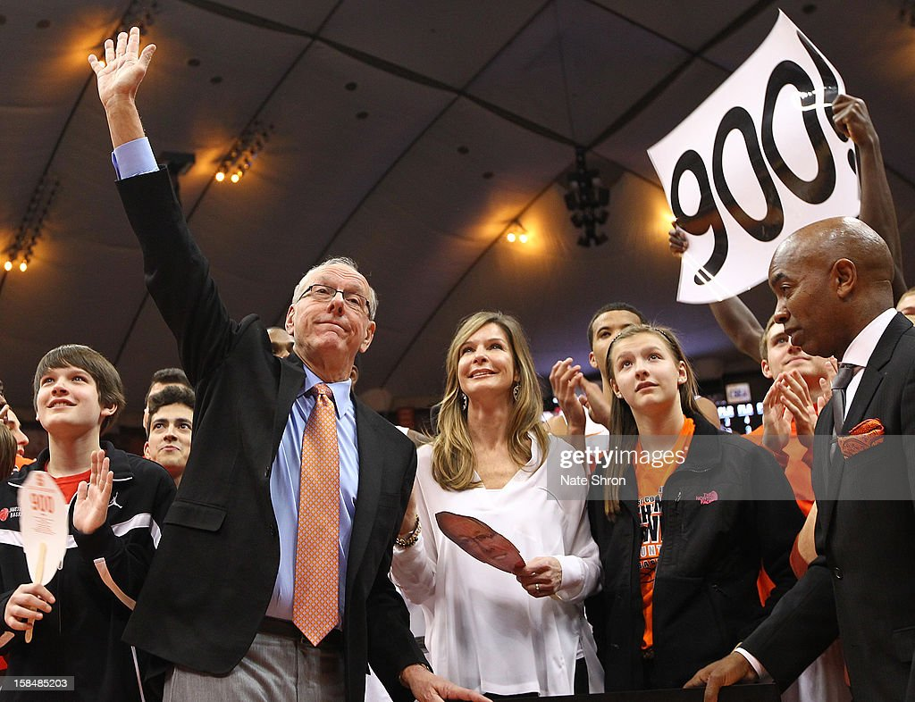 Head coach <a gi-track='captionPersonalityLinkClicked' href=/galleries/search?phrase=Jim+Boeheim&family=editorial&specificpeople=210990 ng-click='$event.stopPropagation()'>Jim Boeheim</a> of the Syracuse Orange waives to the crowd as he stands next to wife Juli Boeheim during a presentation on the court after his 900th career win after the game against the Detroit Titans at the Carrier Dome on December 17, 2012 in Syracuse, New York.