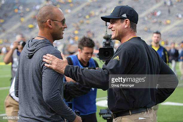 Head coach Jim Harbaugh of the Michigan Wolverines greets baseball great Derek Jeter of the New York Yankees on the sidelines prior to the game...
