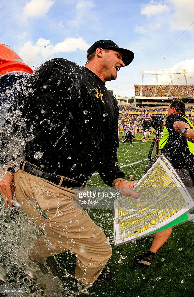 Head coach Jim Harbaugh of the Michigan Wolverines is dumped with water after the Buffalo Wild Wings Citrus Bowl game against the Florida Gators at Orlando Citrus Bowl on January 1, 2016 in Orlando, Florida.