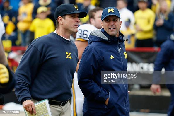 Head coach Jim Harbaugh of the Michigan Wolverines jogs off the fiedl with his brother Baltimore Ravens head coach John Harbaugh following halftime...