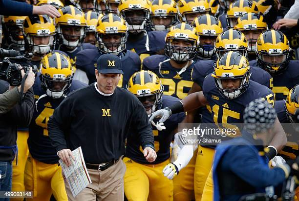Head coach Jim Harbaugh of the Michigan Wolverines leads his team on the field before the start of their game against the Ohio State Buckeyes at...