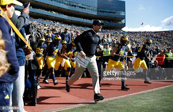 Head coach Jim Harbaugh of the Michigan Wolverines leads the team onto the field to play the Illinois Fighting Illini on October 22 2016 at Michigan...