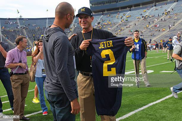 Head coach Jim Harbaugh of the Michigan Wolverines presents baseball great Derek Jeter of the New York Yankees with a jersey prior to the game...