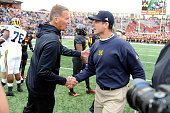 Head coach Jim Harbaugh of the Michigan Wolverines shakes hands with Head coach Randy Edsall of the Maryland Terrapins after the game at Byrd Stadium...