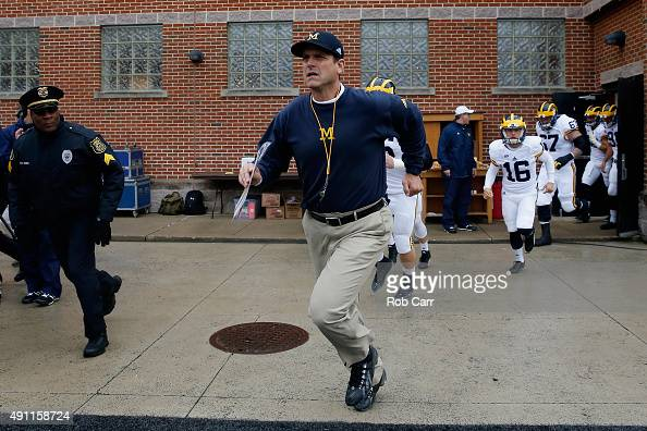 Head coach Jim Harbaugh of the Michigan Wolverines takes the field with his team before the start of their game against the Maryland Terrapins at...