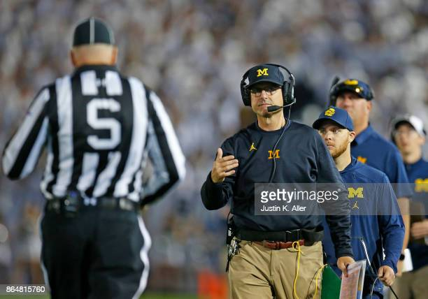 Head coach Jim Harbaugh of the Michigan Wolverines talks with a referee in the first half against the Penn State Nittany Lions on October 21 2017 at...