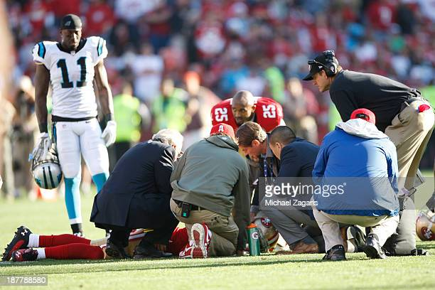 Head Coach Jim Harbaugh of the San Francisco 49ers and the medical staff check out Eric Reid after he received a concussion during the game against...