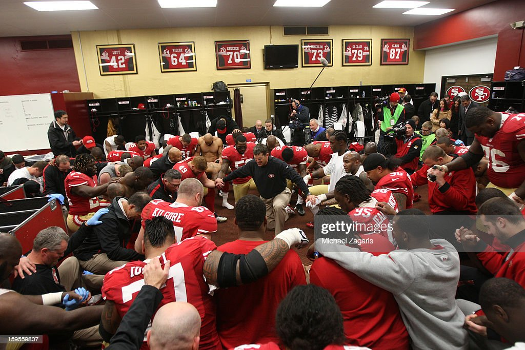 Head Coach Jim Harbaugh of the San Francisco 49ers and the team give thanks in the locker room following the game against the Green Bay Packers at Candlestick Park on January 12, 2012 in San Francisco, California. The 49ers defeated the Packers 45-31.