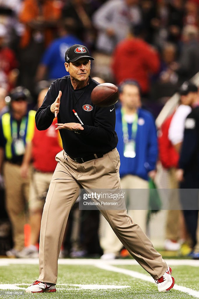Head coach Jim Harbaugh of the San Francisco 49ers catches a pass on the field during warm ups against the Baltimore Ravens during Super Bowl XLVII at the Mercedes-Benz Superdome on February 3, 2013 in New Orleans, Louisiana.