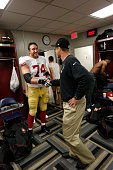 Head Coach Jim Harbaugh of the San Francisco 49ers congratulates Joe Staley in the locker room following the game against the New Orleans Saints at...