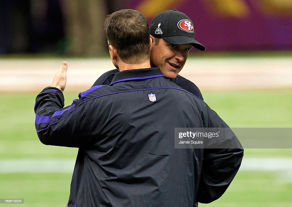 Head coach Jim Harbaugh of the San Francisco 49ers hugs his brother head coach John Harbaugh of the Baltimore Ravens prior to Super Bowl XLVII at the...
