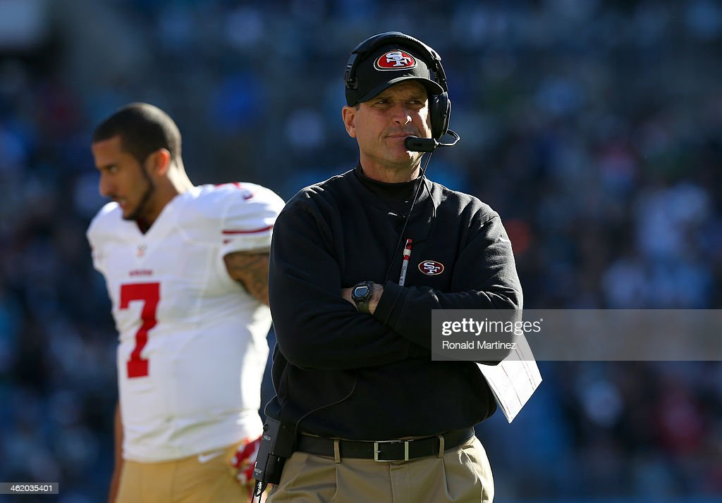 Head coach Jim Harbaugh of the San Francisco 49ers looks on in the second quarter as Colin Kaepernick #7 walks by against the Carolina Panthers during the NFC Divisional Playoff Game at Bank of America Stadium on January 12, 2014 in Charlotte, North Carolina.