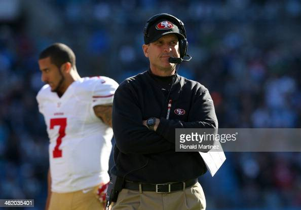 Head coach Jim Harbaugh of the San Francisco 49ers looks on in the second quarter as Colin Kaepernick walks by against the Carolina Panthers during...