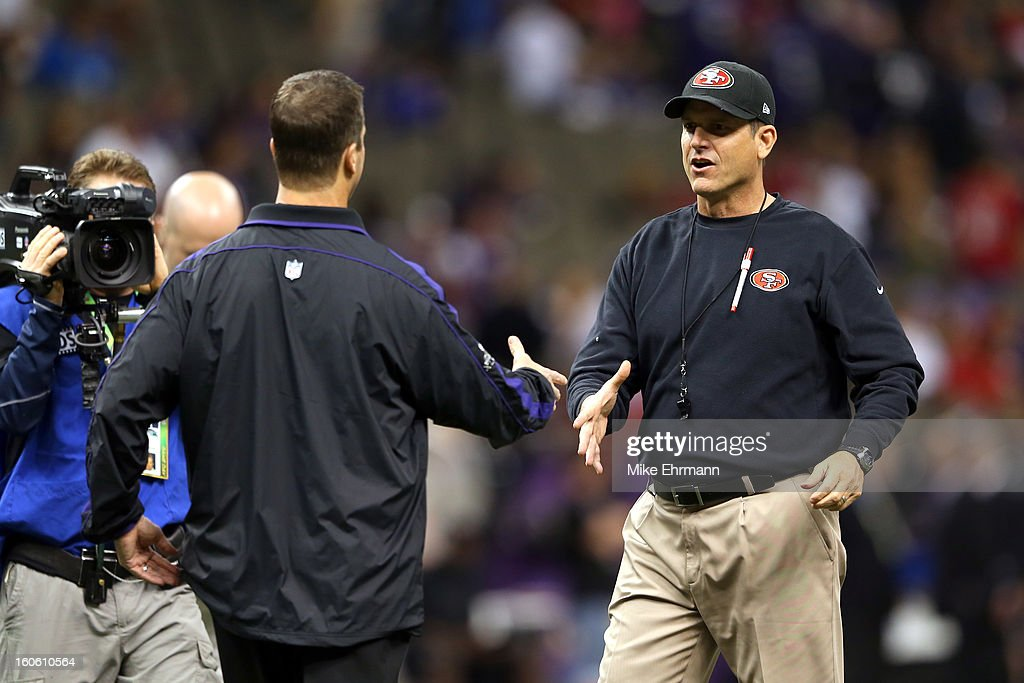 Head coach Jim Harbaugh of the San Francisco 49ers shakes hands with his brother head coach John Harbaugh of the Baltimore Ravens prior to Super Bowl...