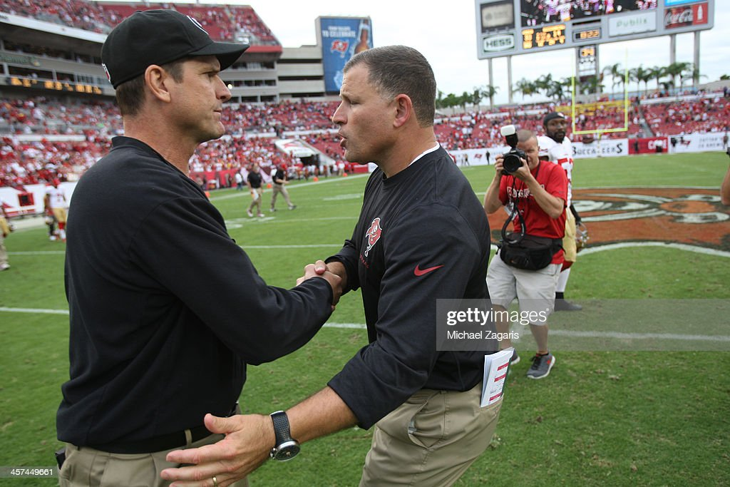 Head Coach Jim Harbaugh of the San Francisco 49ers shakes hands with Head Coach Greg Schiano of the Tampa Bay Buccaneers following the game at...