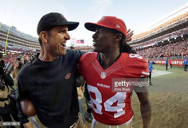 Head coach Jim Harbaugh of the San Francisco 49ers walks off the field with Brandon Lloyd after their game against the Arizona Cardinals at Levi's...