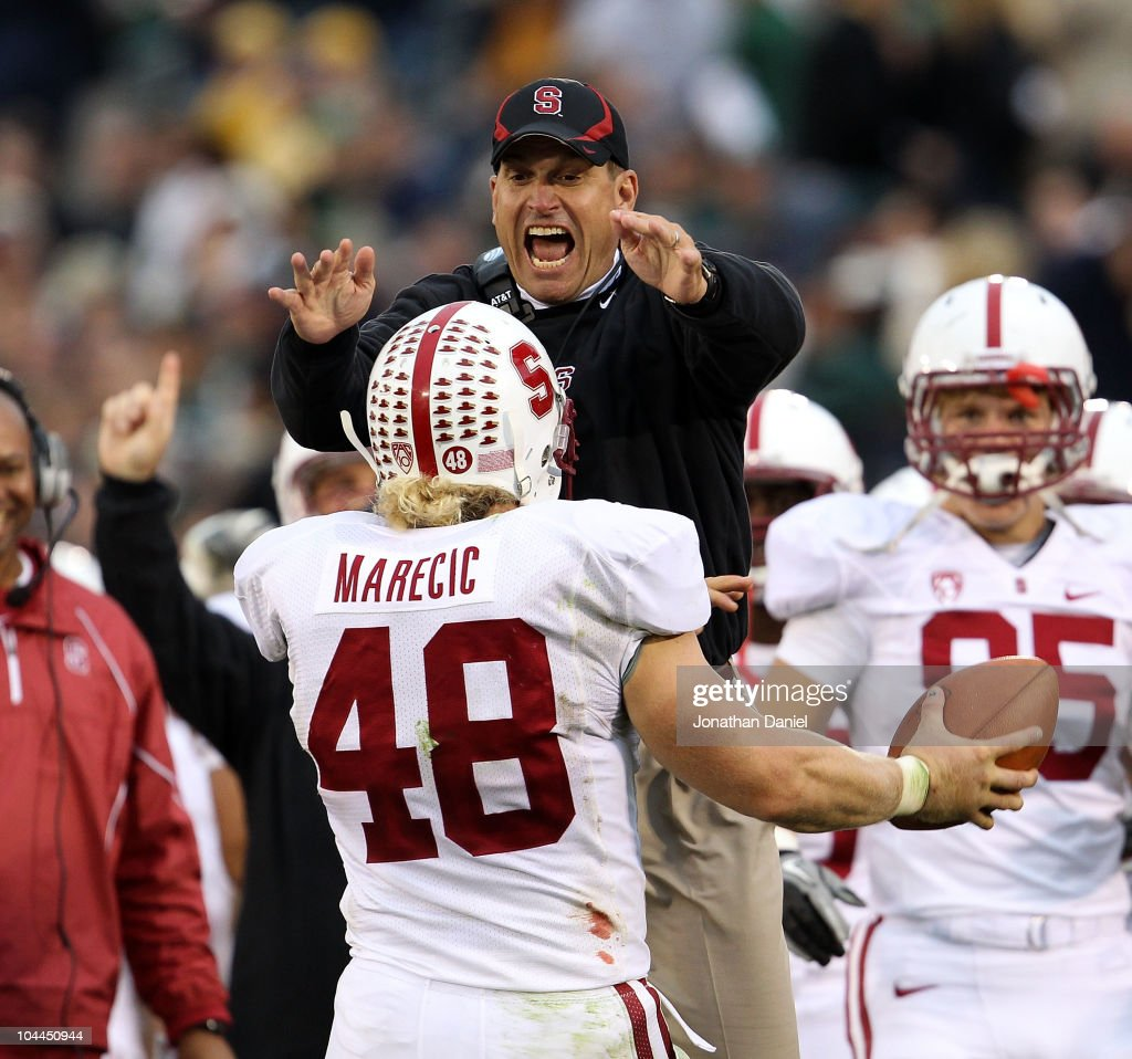 Head coach <a gi-track='captionPersonalityLinkClicked' href=/galleries/search?phrase=Jim+Harbaugh&family=editorial&specificpeople=779595 ng-click='$event.stopPropagation()'>Jim Harbaugh</a> of the Stanford Cardinal jumps to greet Owen Marecic #48 after Marecic intercepted a pass for a touchdown against the Notre Dame Fighting Irish at Notre Dame Stadium on September 25, 2010 in South Bend, Indiana. Stanford defeated Notre Dame 37-14.