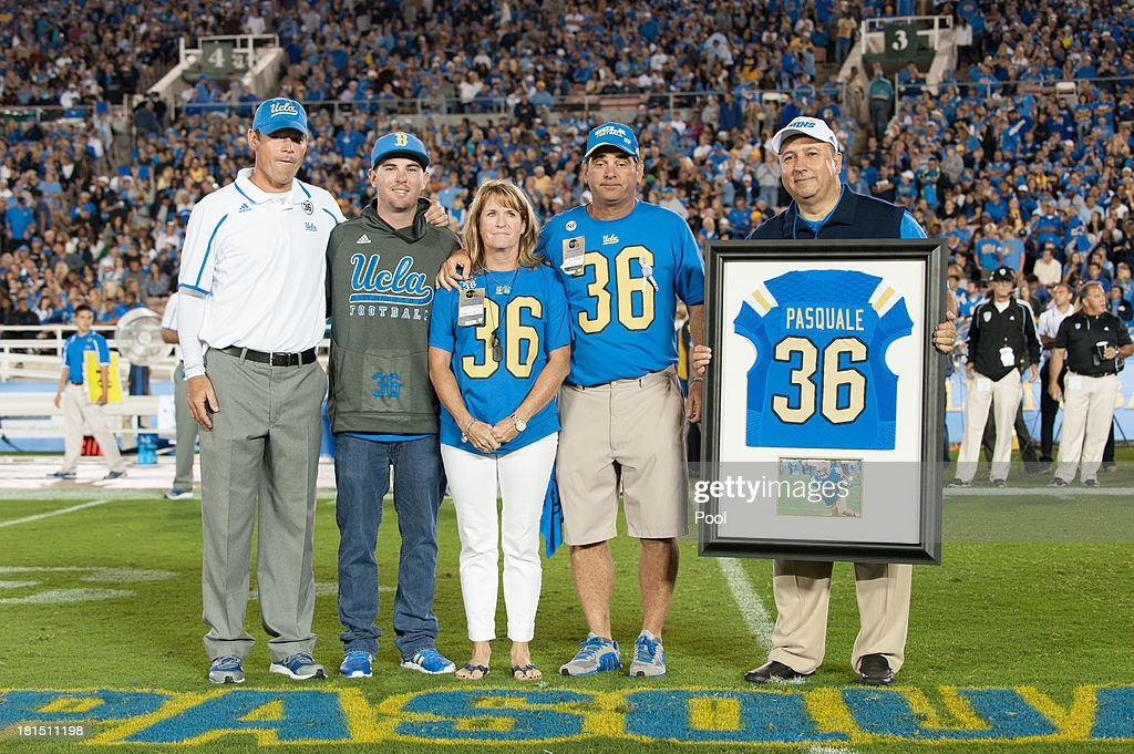 Head Coach <a gi-track='captionPersonalityLinkClicked' href=/galleries/search?phrase=Jim+Mora&family=editorial&specificpeople=210729 ng-click='$event.stopPropagation()'>Jim Mora</a> Jr. of the UCLA Bruins honors the memory of Nick Pasquale #36 with his brother A.J Pasquale, mother Laurie Pasquale, father Mel Pasquale and UCLA Athletic Director Dan Guerrero during the first quarter break against the New Mexico State Aggies at the Rose Bowl on September 21, 2013 in Pasadena, California.
