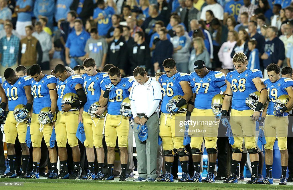 Head coach <a gi-track='captionPersonalityLinkClicked' href=/galleries/search?phrase=Jim+Mora&family=editorial&specificpeople=210729 ng-click='$event.stopPropagation()'>Jim Mora</a>, Jr.of the UCLA Bruins (center, in white) stands with his team in a moment of silence fordeceased UCLA player Nick Pasquale before the game against the New Mexico State Aggies at the Rose Bowl on September 21, 2013 in Pasadena, California.