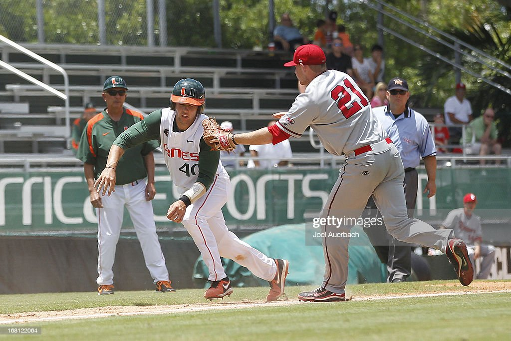 Head coach Jim Morris #3 oohs on as Garrett Kennedy #40 of the Miami Hurricanes is tagged out by Ryan McCormick #21 of the St John's Red Storm in a rundown between third base and home on May 5, 2013 at Alex Rodriguez Park at Mark Light Field in Coral Gables, Florida. Miami defeated St John's 6-4 and swept the weekend series.