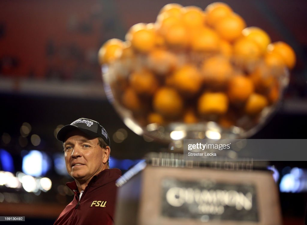 Head coach Jimbo Fisher of the Florida State Seminoles celebrates next to the trophy after they won 31-10 against the Northern Illinois Huskies during the Discover Orange Bowl at Sun Life Stadium on January 1, 2013 in Miami Gardens, Florida.