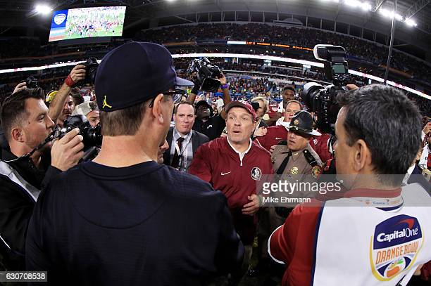 Head coach Jimbo Fisher of the Florida State Seminoles shakes hands with head coach Jim Harbaugh of the Michigan Wolverines after the Seminoles...
