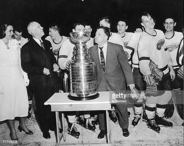 Head coach Jimmy Skinner of the Detroit Red Wings holds his hat in his hand as he leans in to kiss the Stanley Cup trophy after his team won Detroit...