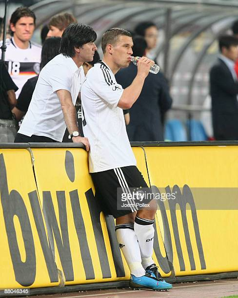 Head coach Joachim Loew and Lukas Podolski are seen after the international friendly match between China and Germany at Shanghai Stadium on May 29...
