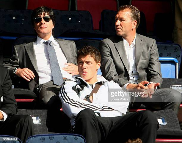 Head coach Joachim Loew assistent coach Andreas Koepke and Sebastian Boenisch of Germany watch the UEFA U21 Championship Group B match between...
