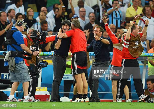 Head coach Joachim Loew goalkeepers' coach Andreas Kopke and assistant coach Hansi Flick celebrate defeating Argentina 10 in the 2014 FIFA World Cup...