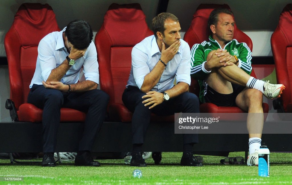 Head coach Joachim Loew (L) of Germany and his assistant coach Hansi Flick (C) show their dejection after the UEFA EURO 2012 semi final match between Germany and Italy at the National Stadium on June 28, 2012 in Warsaw, Poland.