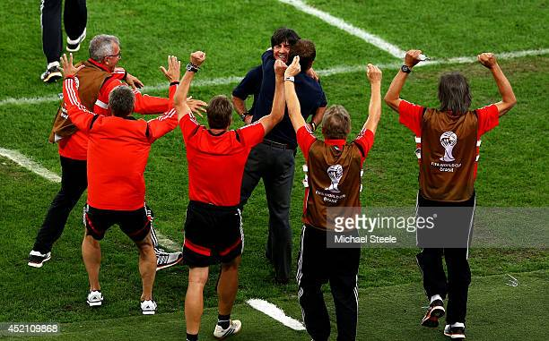 Head coach Joachim Loew of Germany celebrates with assistant coach Hansi Flick and staff after his team's first goal in extra time by Mario Goetze...