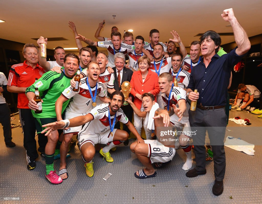 Head Coach <a gi-track='captionPersonalityLinkClicked' href=/galleries/search?phrase=Joachim+Loew&family=editorial&specificpeople=215315 ng-click='$event.stopPropagation()'>Joachim Loew</a> of Germany (R) celebrates with players and Angela Merkel,Chancellor of Germany in the Germany dressing room after the 2014 FIFA World Cup Brazil Final match between Germany and Argentina at Maracana on July 13, 2014 in Rio de Janeiro, Brazil.