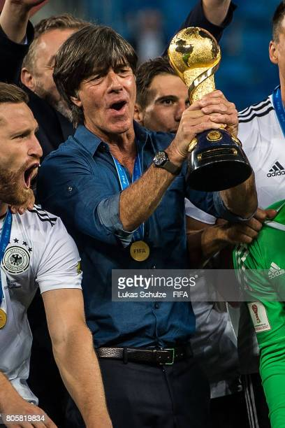 Head Coach Joachim Loew of Germany holds the trophy after winning the FIFA Confederations Cup final match between Chile and Germany at Saint...