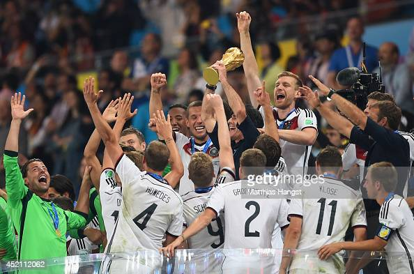 Head coach Joachim Loew of Germany lifts the World Cup trophy with his players after defeating Argentina 10 in extra time during the 2014 FIFA World...