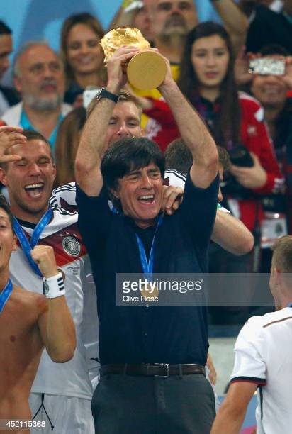 Head coach Joachim Loew of Germany raises the World Cup trophy after defeating Argentina 10 in extra time during the 2014 FIFA World Cup Brazil Final...