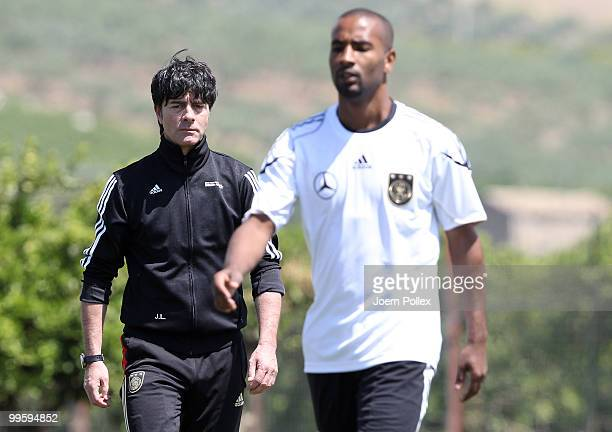 Head coach Joachim Loew of Germany talks to Cacau of Germany during the German National Team training session at Verdura Golf and Spa Resort on May...