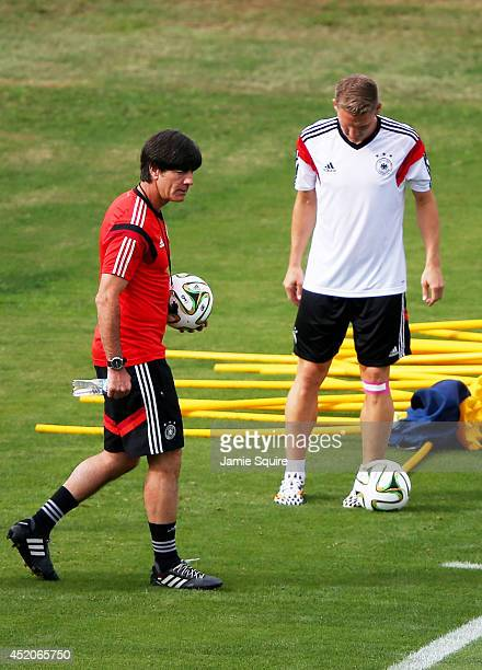 Head coach Joachim Loew of Germany walks out onto the pitch as Bastian Schweinsteiger of Germany warms up during the Germany training session ahead...