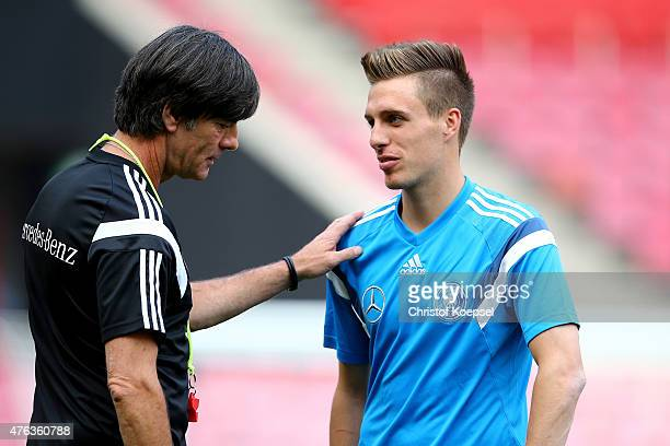 Head coach Joachim Loew speaks to Patrick Herrmann of Germany during a training session ahead of their international friendly match against USA at...