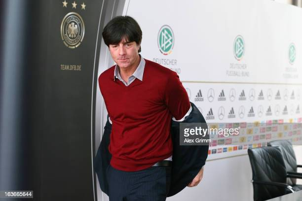 Head coach Joachim Loew takes off his jacket as he leaves a Germany press conference at the DFB headquarters on March 14 2013 in Frankfurt am Main...