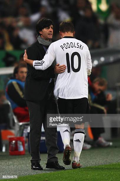 Head coach Joachim Loew talks to Lukas Podolski after his substitution during the FIFA 2010 World Cup Qualifier Group 4 match between Germany and...