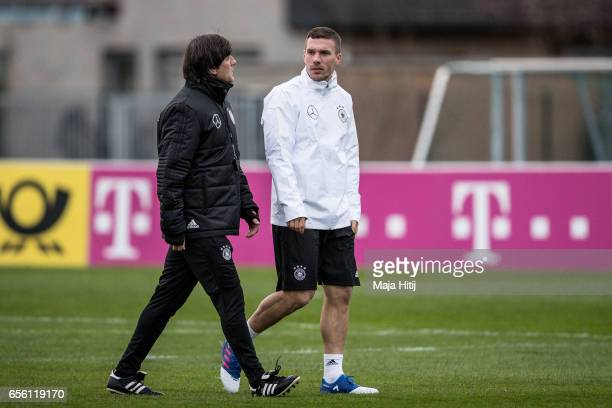Head coach Joachim Loew talks to to Lukas Podolski during a training of the German national team ahead of the international friendly match against...