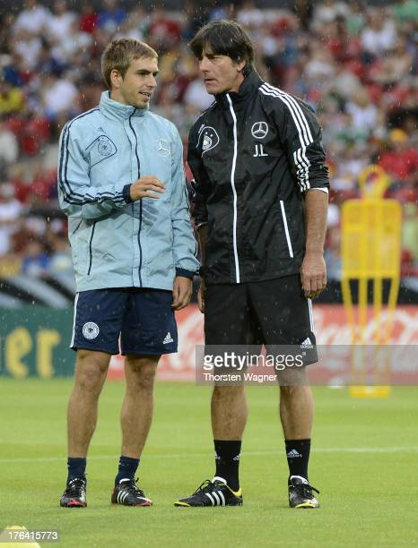 Head coach Joachim Loew talks with Philipp Lahm during the German National Football Team trainings session at Coface Arena on August 12 2013 in Mainz...