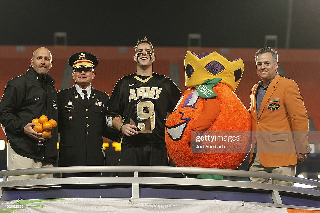 Head Coach Joe Alberici (L) holds the game trophy and Garrett Thul #9 holds the MVP trophy of the Army Black Knights during the award presentation after defeating the Michigan Wolverines 12-1 during the 2013 Orange Bowl Lacrosse Classic on March 2, 2013 at SunLife Stadium in Miami Gardens, Florida.