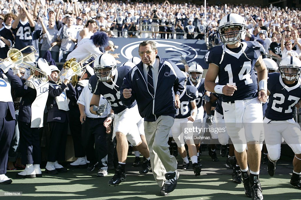 Head Coach Joe Paterno runs onto the field with Anthony Morelli #14 of The Penn State Nittany Lions prior to a game against the Minnesota Gophers on October 1, 2005 at Beaver Stadium in State College, Pennsylvania. Penn State defeated Minnesota 44-14.